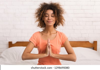 African-american woman sitting in namaste yoga position and relaxing on bed in the morning
