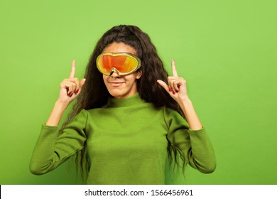 African-american young brunette woman's portrait in ski mask on green studio background. Concept of human emotions, facial expression, sales, ad, winter sport and holidays. Smiling, pointing up.