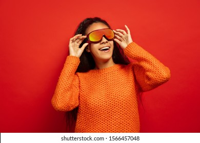 African-american young brunette woman's portrait in ski mask on red studio background. Concept of human emotions, facial expression, sales, ad, winter sport and holidays. Looking up, smiling.