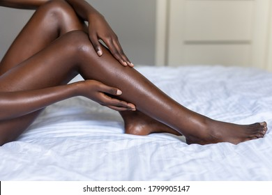 African-American young woman in white lingerie sitting on bed sheet and massaging her legs.