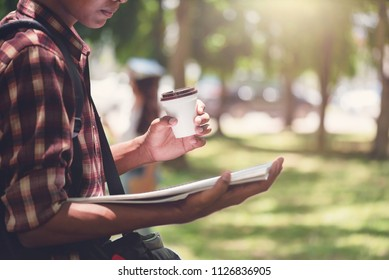 African-Asian student man reading book and drinking  hot coffee in campus