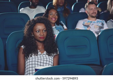 Africanl sitting alone and watching movie in cinema.