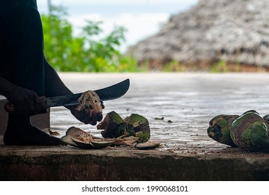 Afrikan dark skinned man is being openning a fresh coconut with machete, in motion, hands only Tanzania, Afrika