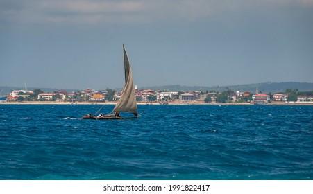 Afrikan fishing sailboat Ngalawa  goes on the deep blue waves near Mnemba island, Tanzania