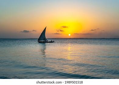Afrikan fishing sailboat Ngalawa  on beaitiful sunset background near Mnemba island, Tanzania