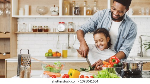 Afro ameriacan father teaching his little daughter to cut vegetables, cooking salad. Cooking healthy food together concept
