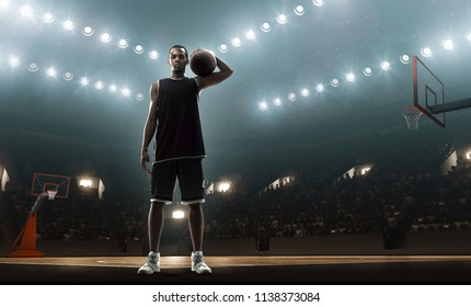 Afro american athlete. Basketball player holding a ball on a flood lit basketball arena