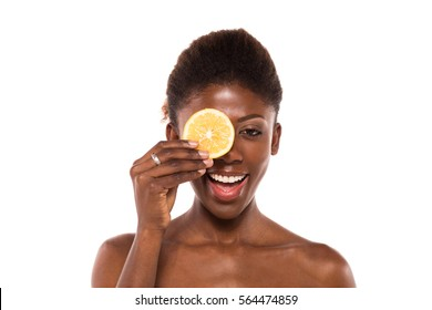 afro american black woman posing with two slices of lemon on white background for skin and body care