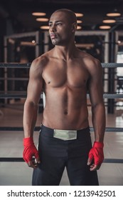 Afro American boxer, his hands wrapped in red bandage, is looking away while standing in pose in gym