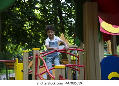 Afro american boy plays summer evening at the playground
