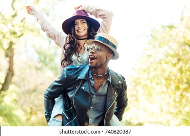 Afro american boyfriend giving piggyback to his girlfriend while walking in the park