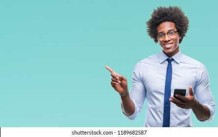 Afro american business man texting using smartphone over isolated background very happy pointing with hand and finger to the side