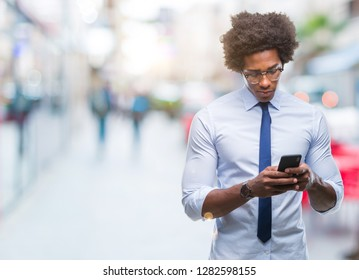 Afro american business man texting using smartphone over isolated background with a confident expression on smart face thinking serious
