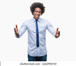 Afro american business man wearing glasses over isolated background looking at the camera smiling with open arms for hug. Cheerful expression embracing happiness.