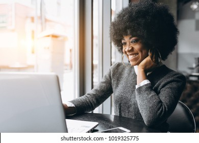 Afro american business woman working on laptop in a cafe