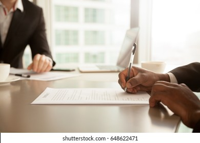 Afro american businessman signing partnership agreement concept, focus on male hand putting signature, concluding official contract on meeting, african entrepreneur making profitable deal, close up