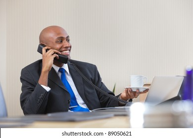 Afro American businessman talking on telephone while holding cup