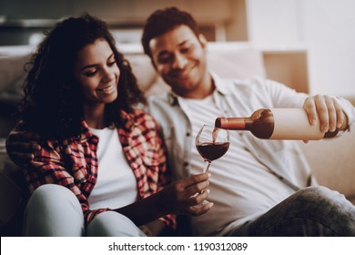 Afro American Couple Drinking On A Couch. Weekend Concept. Chilling On Sofa. Holiday Resting. Smiling Together. Having Fun. Romantic Date. Cheerful Sweethearts. Bottle Of Wine. Happy Family.