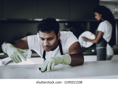 Afro American Couple Kitchen Cleaning Concept. Dish Washing. Table Cleaning. Protective Green Gloves. Household Problem. Dust Wipe Cleaner. Housecleaning Weekend. Healthy Lifestyle.