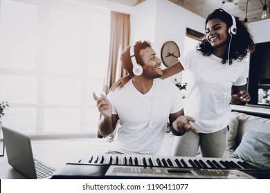 Afro American Couple Listening With Headphones Synthesizer Playing. Happy Songwriter. Morning Leisure. Digital Format Sound Record. Working Musician. Musical Hobby. Taking A Rhytm.