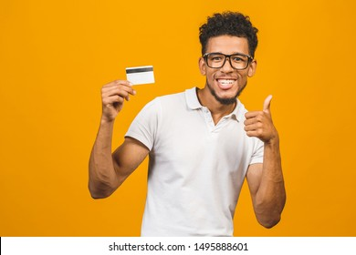 Afro american customer man holding credit card standing over isolated yellow background happy with big smile doing ok sign, thumb up with fingers, excellent sign