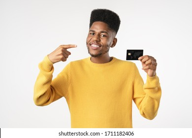 Afro american customer man holding credit card pointing with finger standing over isolated white background