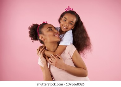 Afro American daughter on piggy back ride with mother. Isolated on pink background. Studio portrait.