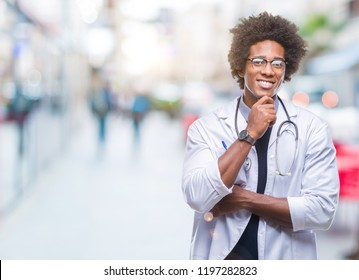 Afro american doctor man over isolated background looking confident at the camera with smile with crossed arms and hand raised on chin. Thinking positive.