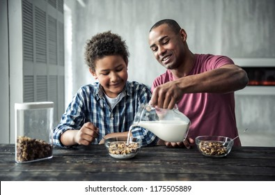 Afro American father and son in casual clothes are smiling while eating muesli at the wooden table together at home