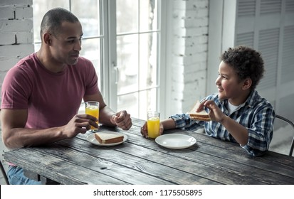 Afro American father and son in casual clothes are talking and smiling while eating at the wooden table together at home