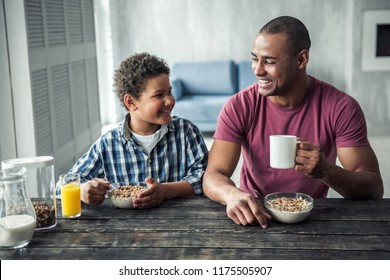 Afro American father and son in casual clothes are talking and smiling while having breakfast together at home