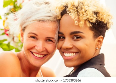 afro american female in the role of the groom and short blonde haired bride in blue dress in ceremony under wedding arch in tropical beach