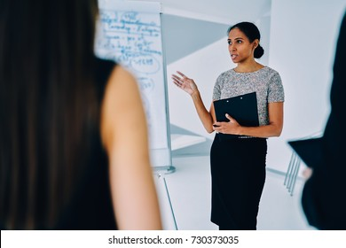 Afro american female speaker talking during presentation explaining main points and strategies to auditory, professional marketing expert making speech on corporate conference share planning