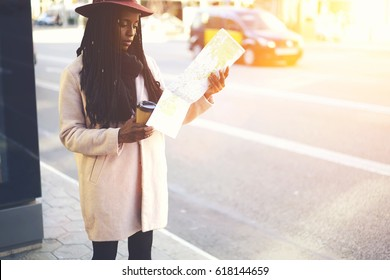 Afro american female tourist dressed in style hat and pink coat searching right direction on map to getting to appointed place in new town.Young traveller walking on streets of city with coffee