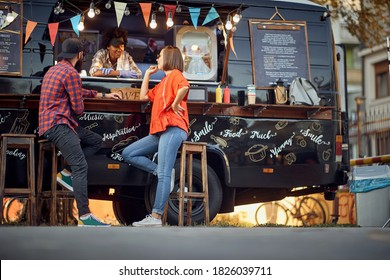 Afro american food truck employee taking orders from customers