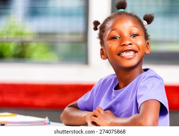 Afro american girl in elementary school happy at her desk.
