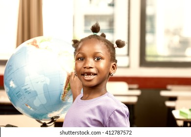 Afro american girl at elementary school with earth globe learning geography.
