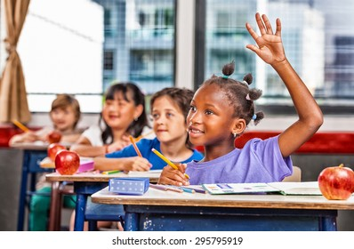Afro american girl raising hand in a multi race classroom.