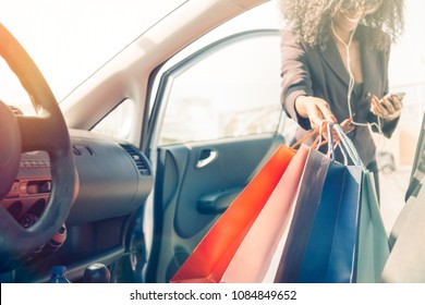 afro american girl with shopping bags in car using cell phone
