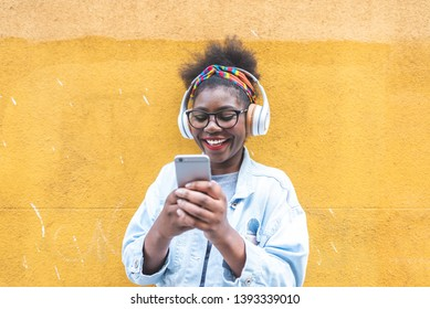 Afro American Girl Using Mobile Phone Outdoors. Latin American Teenager Having Fun. Black Girl Using Cellphone and Laughing.Youth Concept.