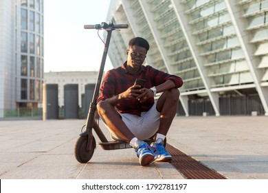 afro american guy sits with an electric scooter and uses a smartphone in the city, student with eco transport holds a phone