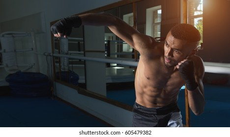 Afro american male boxer. Young man boxing workout in a fitness club. Muscular strong man on background boxing gym.