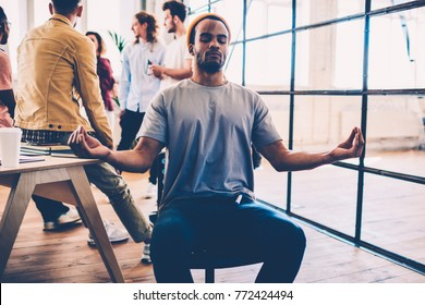 Afro american male member of working team sitting with closed eyes in lotus pose feeling peace breathing while colleague having discussion, skilled designer finding inspiration in meditation on work
