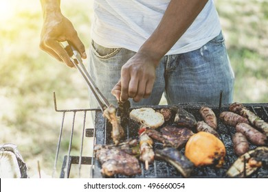 Afro american man cooking meat on barbecue - Chef putting some sausages and pepperoni on grill in park outdoor - Concept of eating outdoor during summer time - Vintage retro filter with sun halo flare
