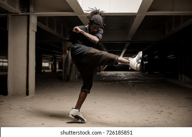 Afro american man with dreadlocks and in black clothes and white sport shoes lifting the leg up. Full length
