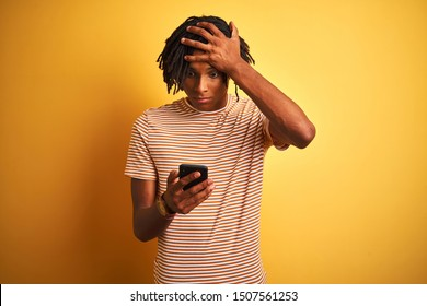 Afro american man with dreadlocks using smartphone over isolated yellow background stressed with hand on head, shocked with shame and surprise face, angry and frustrated. Fear and upset for mistake.