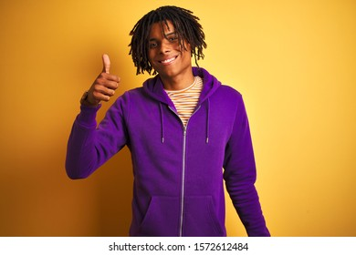 Afro american man with dreadlocks wearing purple sweatshirt over isolated purple background doing happy thumbs up gesture with hand. Approving expression looking at the camera with showing success.