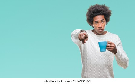 Afro american man drinking cup of coffee over isolated background pointing with finger to the camera and to you, hand sign, positive and confident gesture from the front