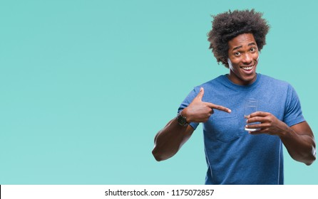 Afro american man drinking glass of water over isolated background very happy pointing with hand and finger