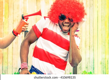 Afro american man fan of football have fun with bizarre look for international sport event - Black african male with funny wig is screaming deafened by unpleasant noise - Concept of health danger